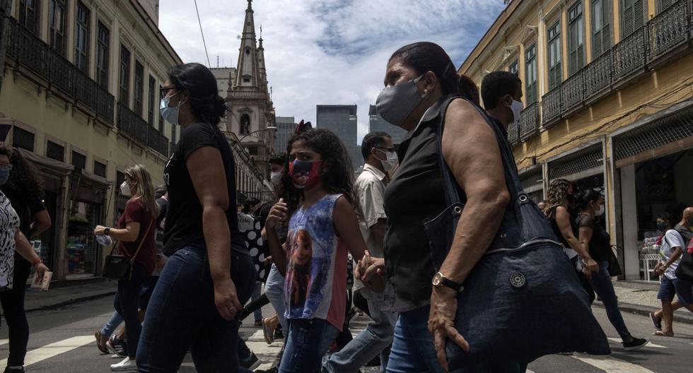 Personas con mascarillas caminan por un paso de peatones en el centro de Río de Janeiro, Brasil, el 8 de diciembre de 2020 en medio de la pandemia del coronavirus. (MAURO PIMENTEL / AFP).