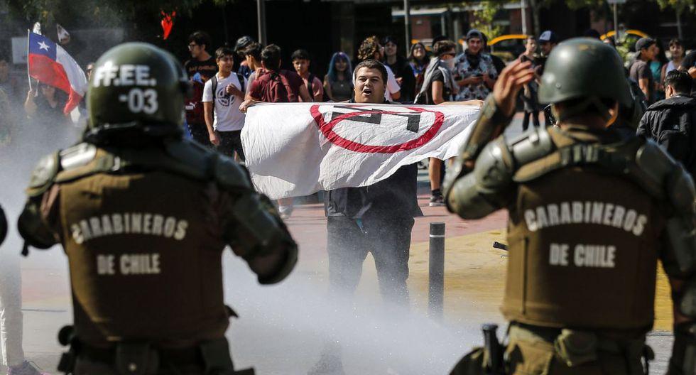 Un tenso encontrón protagonizaron este sábado dos grupos de manifestantes en Santiago de Chile. Algunos con una fotografía de Pinochet en brazos gritaron contra una nueva Constitución, en sentido opuesto a los que pedían su aprobación. (AFP).