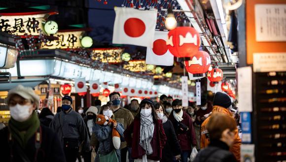 Personas con máscaras faciales caminan por la calle comercial del templo Sensoji en el distrito de Asakusa, en Tokio, el pasado 2 de enero de 2021. (Behrouz MEHRI / AFP)