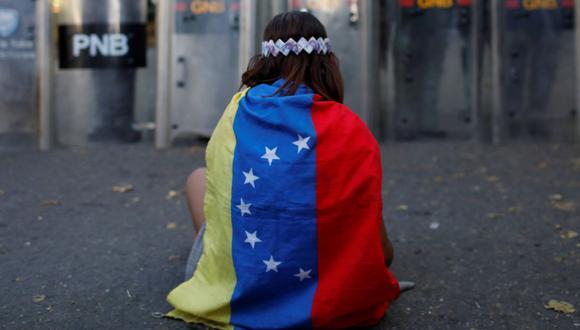 Imagen referencial. Una niña lleva una bandera venezolana en una calle de la capital Caracas, Venezuela, el 20 de enero de 2018. (REUTERS/Marco Bello).