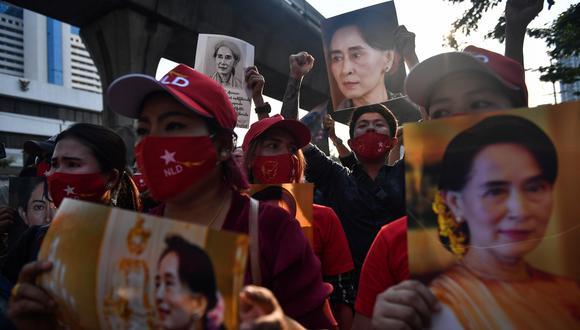 Migrantes en Birmania protestan hoy sosteniendo imágenes de la líder política Aung San Suu Kyi frente a la embajada del país en Bangkok, tras el golpe militar. (Foto: AFP)