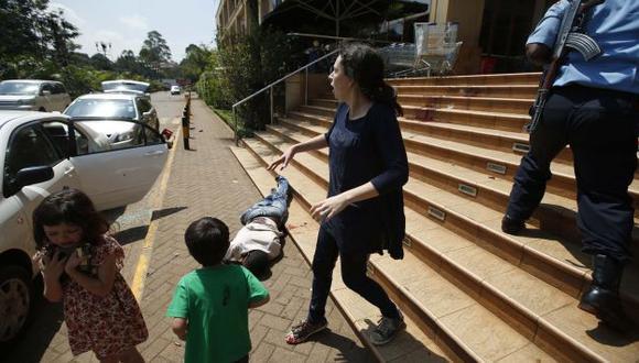 Madre con sus hijos sale aterrorizada del local en Nairobi. (Reuters)