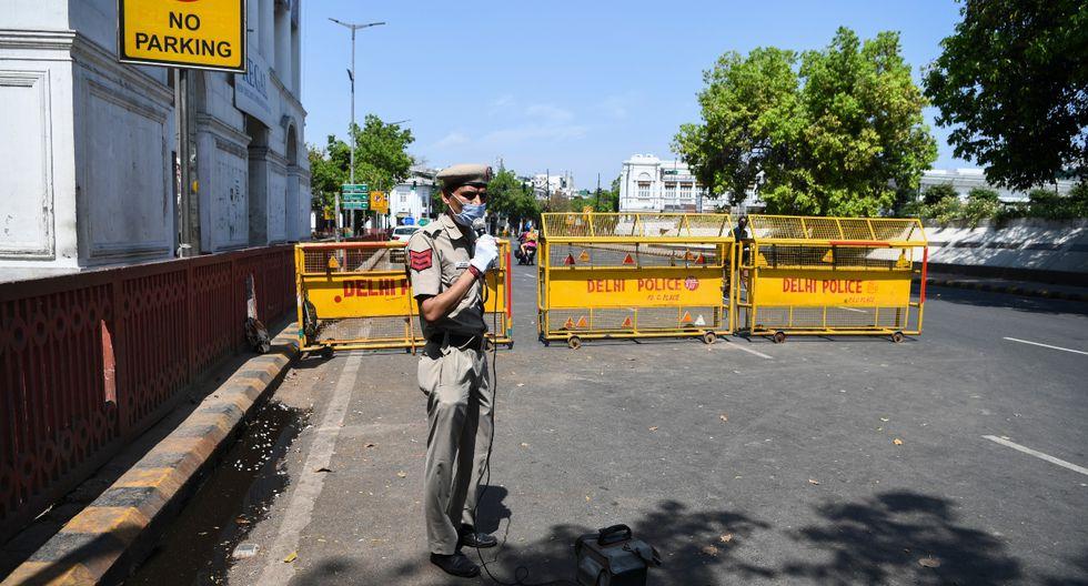 """Un policía usa un altavoz para pedirle a las personas de Nueva Delhi, India que """"se queden en casa"""". (AFP)."""