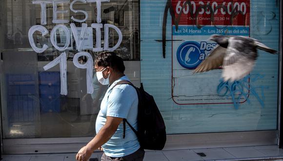 Una persona pasa junto a una farmacia donde se realizan pruebas de COVID-19 en la comuna de Recoleta, que fue puesta en cuarentena para frenar la propagación del nuevo coronavirus, en Santiago. (Foto: AFP/MARTIN BERNETTI)