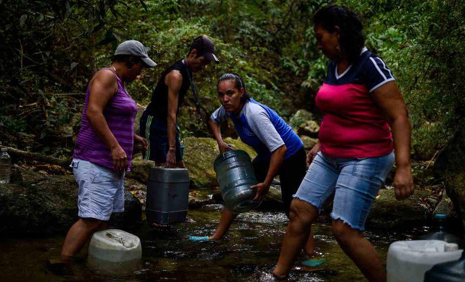 """La gente llena los recipientes con agua de un arroyo en la montaña Wuaraira Repano, también llamada """"El Ávila"""", en Caracas. (Foto: AFP)"""