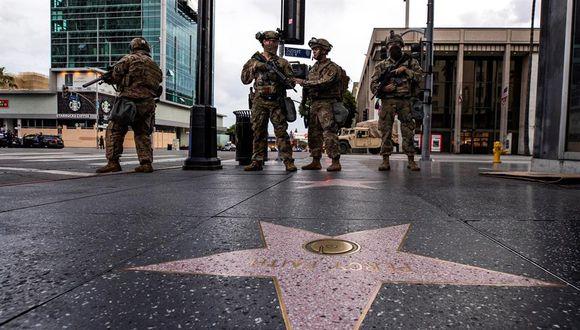 Soldados de la Guardia Nacional hacen guardia en el Paseo de la Fama durante el toque de queda mientras cientos de manifestantes salieron a la calle para manifestarse tras la muerte de George Floyd, en Hollywood, California. (EFE / EPA / ETIENNE LAURENT)