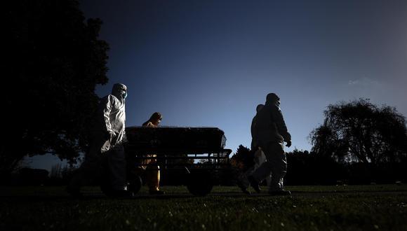 Trabajadores funerarios trasladan el féretro de una persona muerta por covid-19. EFE/ Juan Ignacio Roncoroni/Archivo