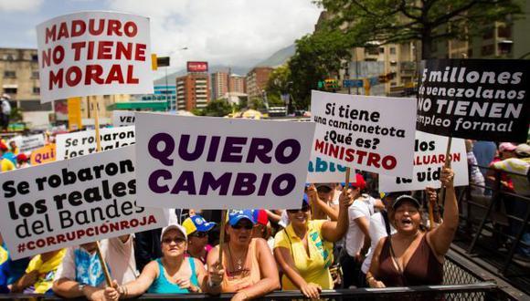 DEMANDA. Ciudadanos venezolanos con carteles exigen un cambio de dirección en un país en crisis. (EFE)