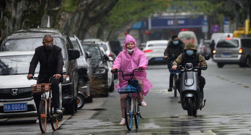 Las personas que usan máscaras viajan a lo largo de una calle en Wuhan, en la provincia central de Hubei de China. (Foto: AFP/Noel Celis)