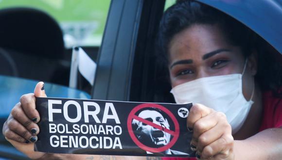 """Un manifestante sostiene un cartel que dice """"Bolsonaro genocida fuera"""" durante una caravana para protestar contra el gobierno del presidente brasileño Jair Bolsonaro en Sao Paulo, Brasil. (REUTERS/Carla Carniel)."""