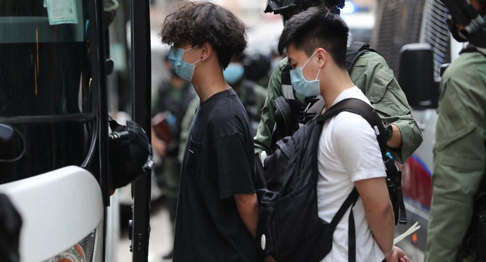 Los oficiales de policía escoltan a los hombres a una camioneta de la policía luego de una manifestación durante el Día Nacional de China en Hong Kong. (AFP / May JAMES).
