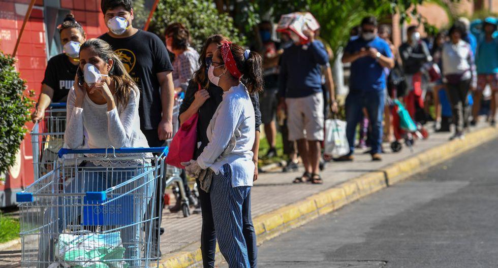Supermercados, farmacias y locales de servicios públicos de siete comunas en Santiago amanecieron este jueves con grandes aglomeraciones de personas apuradas por hacer compras o trámites, antes del comienzo de una cuarentena total esta noche por el coronavirus. (AFP).