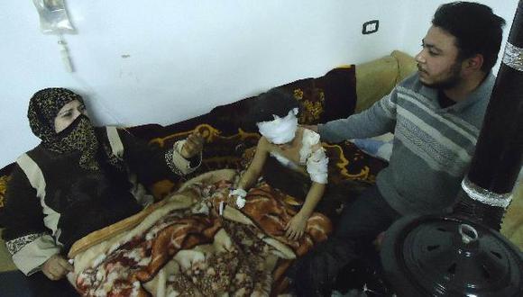 Una niña herida por el bombardeo en Homs, junto a sus padres. (Reuters)