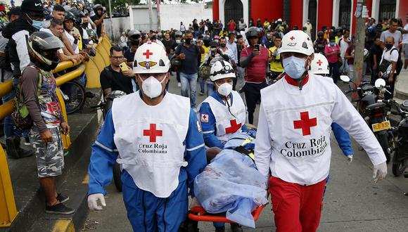 Miembros de la Cruz Roja Colombiana levantan el cuerpo sin vida de un hombre hoy, durante las manifestaciones en el sector La Luna, en Cali, Colombia. (EFE/Ernesto Guzmán Jr)