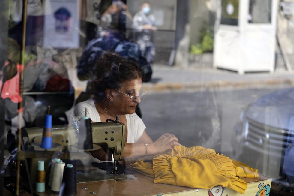 Claudette, una costurera libanesa de 60 años, trabaja en su tienda recién restaurada en el vecindario Gemmayzeh de Beirut, Líbano. (JOSEPH EID / AFP).