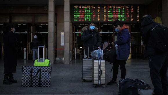 Personas con mascarillas protectoras llevan sus pertenencias fuera de la estación de tren de Beijing en medio de la pandemia de la enfermedad por coronavirus en Beijing. (EFE/WU HONG).