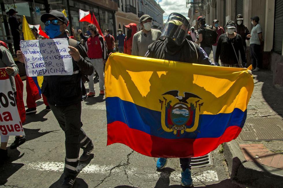 """Un manifestante sostiene una bandera ecuatoriana mientras otra sostiene un cartel que dice """"Si las guerras ahora son biológicas, es hora de disolver el ejército e invertir en medicina"""" durante una demostración contra los salarios más bajos y los recortes presupuestarios impuestos por el gobierno en medio de la nueva pandemia de coronavirus. en el centro de Quito, el 25 de mayo de 2020. (AFP / Cristina Vega Rhor)."""