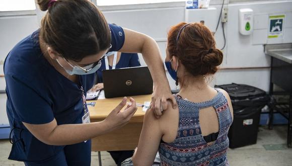 La enfermera chilena María Paz Herreros, de 32 años, quien fue la primera en inocular a un paciente contra el COVID-19 en Chile, inyecta a una mujer la vacuna china Sinovac, en el Hospital Metropolitano de Santiago, el 26 de febrero de 2021. (Foto de MARTIN BERNETTI / AFP).