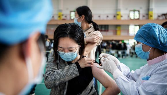 Esta foto de archivo tomada el pasdo 28 de abril de 2021 muestra a estudiantes universitarios haciendo cola para recibir la vacuna contra el coronavirus  en el Grupo Nacional Biotec de China (CNBG), en una universidad de Wuhan. (STR / AFP)