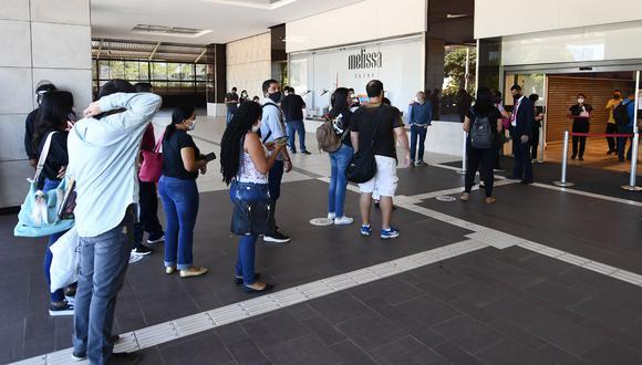 La gente espera en la cola para que le revisen la temperatura corporal antes de ingresar a un centro comercial en Brasilia el 27 de mayo de 2020, el primer día de reapertura comercial en la ciudad en medio de la pandemia de coronavirus COVID-19. (Foto: AFP/EVARISTO SA)