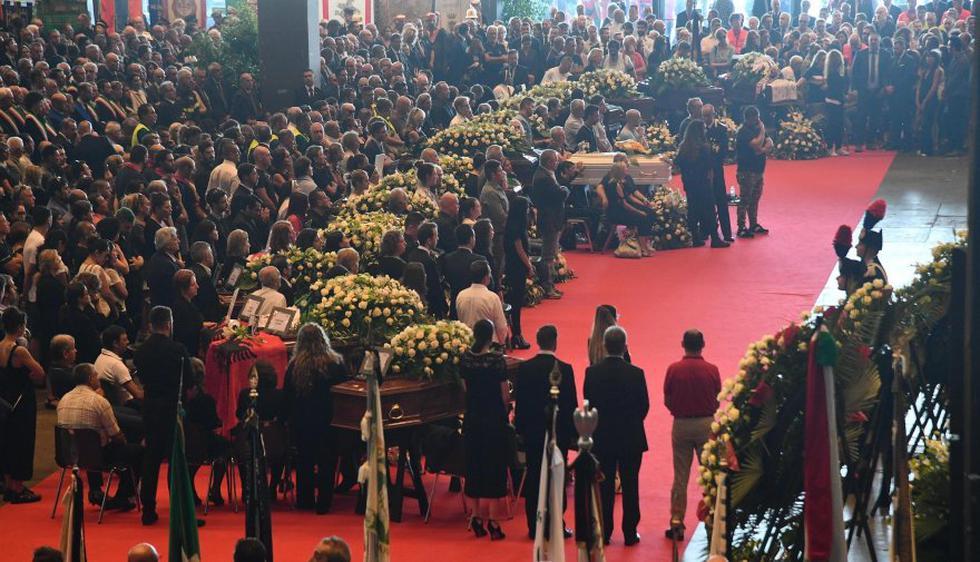 En uno de los pabellones del recinto ferial de la ciudad, cubiertos por coronas de rosas blancas, se habían depositado los féretros de 19 de las víctimas. (Foto: EFE)