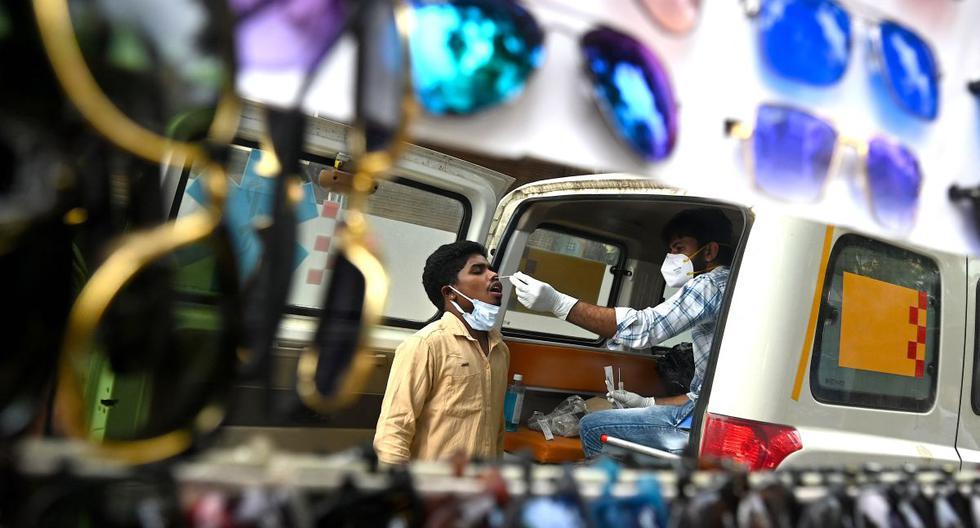 Un trabajador de la salud que recolecta una muestra de hisopo de un hombre para detectar el coronavirus se ve reflejado a través de un espejo en un puesto de carretera en Gurgaon (India), el 13 de junio de 2021. (Money SHARMA / AFP).