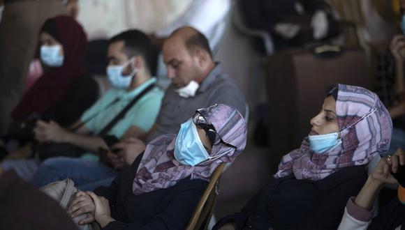 Fotografía de archivo del 27 de septiembre de 2020 de palestinos con mascarillas sentados junto a su equipaje mientras esperan cruzar el cruce fronterizo con Egipto Rafah en el sur de la Franja de Gaza. (Foto referencial: AP Foto/Khalil Hamra, Archivo).