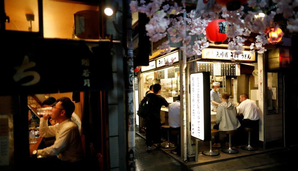 La gente disfruta de bebidas y cenas después del brote de la enfermedad del coronavirus (COVID-19) en el callejón de bares parcialmente reabierto en el distrito de Shinjuku en Tokio, Japón. (REUTERS/Issei Kato).