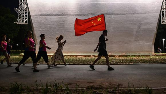 En esta foto tomada el 4 de septiembre de 2020, un hombre camina con la bandera nacional china en un parque junto al río Yangtze en Wuhan, provincia central china de Hubei. (AFP/Hector Retamal).