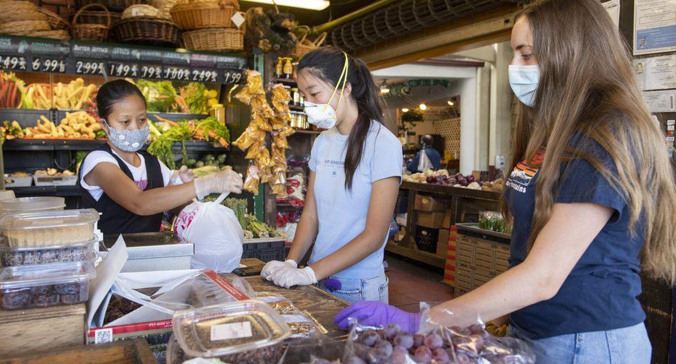 Mira Kwon (centro), la estudiante de 16 años que dirige en Los Ángeles un servicio gratuito de entrega de comestibles para mayores en medio del coronavirus, es vista comprando en una tienda junto a su compañera Betsy Bass (derecha). (VALERIE MACON / AFP)