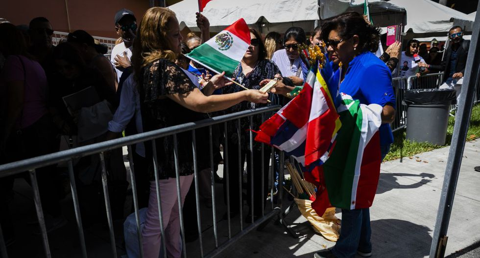 A woman sells flags to the fans in line outside of the Miami-Dade County Auditorium during a public funeral for the late singer Jose Jose in Miami, Florida on October 6, 2019. - The artist born Jose Romulo Sosa Ortiz, who died last Saturday at age 71, is being honored at a funeral home southeast of Miami. (Photo by Eva Marie UZCATEGUI / AFP)