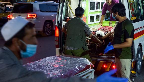 El personal médico lleva a un herido a un hospital en una ambulancia después de dos poderosas explosiones, que mataron al menos a seis personas, fuera del aeropuerto de Kabul el 26 de agosto de 2021 (Foto: Wakil KOHSAR / AFP).