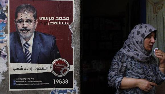 Mujer cerca del afiche del candidato Mohamed Mursi. (AP)