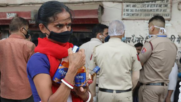 Imagen referencial. Mujer con una máscara de protección es vista en inmediaciones de una licorería en Nueva Delhi, India. (EFE/RAJAT GUPTA).