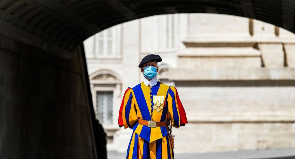 En esta foto de archivo tomada el 18 de mayo de 2020, un guardia suizo con una máscara facial monta guardia junto a la Basílica de San Pedro. (AFP / Vincenzo PINTO).