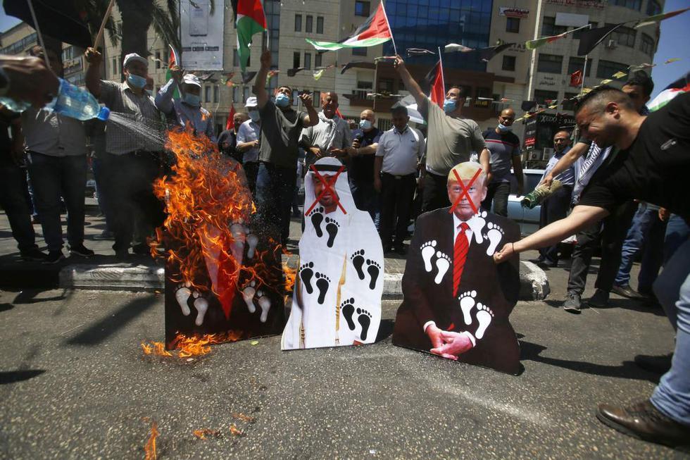 Palestinos queman fotografías del presidente de Estados Unidos, Donald Trump, el príncipe heredero de Abu Dhabi, Mohammed bin Zayed al-Nahyan, y el primer ministro israelí, Benjamin Netanyahu, durante una protesta en la ciudad cisjordana de Nablus. (AP/Majdi Mohammed).