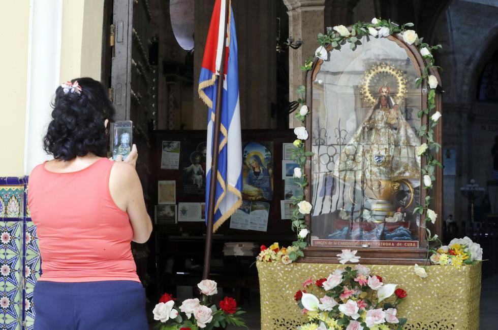 Una mujer le toma una foto a la imagen de la Virgen de la Caridad del Cobre, en La Habana, Cuba. (EFE/Ernesto Mastrascusa).