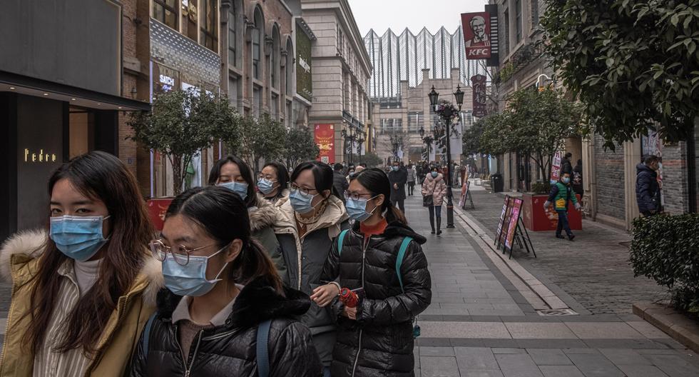 Personas con mascarillas protectoras caminan frente a un centro comercial el día del primer aniversario del cierre de Wuhan, en Wuhan, China, el 23 de enero de 2021. (EFE/EPA/ROMAN PILIPEY).