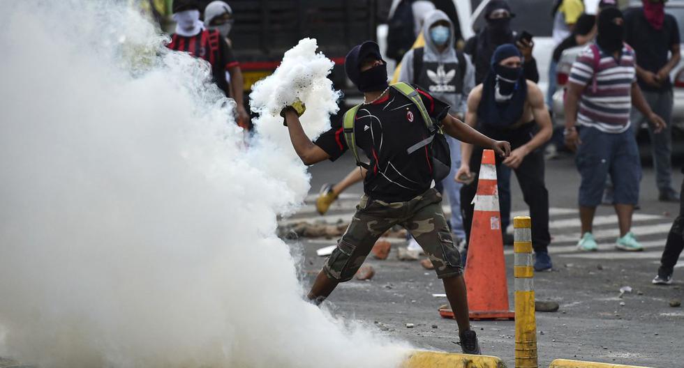 Un manifestante lanza una lata de gas lacrimógeno a los agentes de la policía antidisturbios durante una protesta contra el gobierno en Cali, Colombia, el 10 de mayo de 2021. (Luis ROBAYO / AFP).