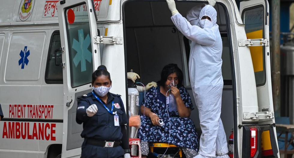 Un trabajador de la salud atiende a una paciente de coronavirus Covid-19 en un hospital de Bombay, India. (Foto: Punit PARANJPE / AFP).