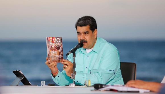 Imagen del folleto difundido por la Presidencia venezolana que muestra al presidente de Venezuela, Nicolás Maduro, mostrando el libro que el expresidente boliviano Evo Morales le entregó durante su visita al país, durante un anuncio televisado en el estado de La Guaira, Caracas. (AFP/Venezuelan Presidency).