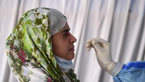 Un trabajador de la salud realiza un test de coronavirus a una mujer en un centro de pruebas en Srinagar, el pasado 12 de abril de 2021. (Foto de TAUSEEF MUSTAFA / AFP).