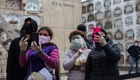 Familiares de un fallecido por coronavirus COVID-19 graban y transmiten por videollamada el funeral en el cementerio El Ángel en Lima (Perú). (EFE/Sergi Rugrand).