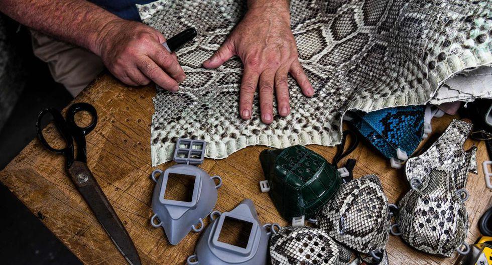 Brian Wood hace máscaras faciales de piel de serpiente dentro de su taller en Delray Beach, a unas 52 millas al norte de Miami, el 21 de mayo de 2020. (AFP / CHANDAN KHANNA).