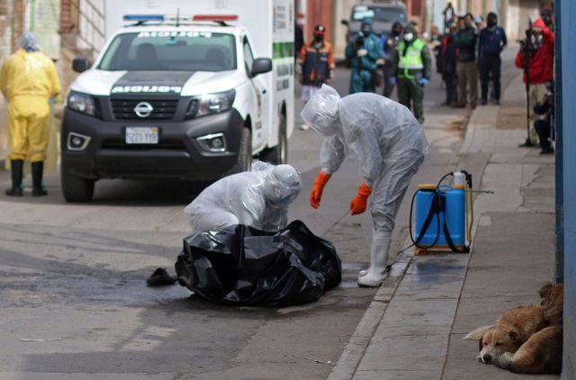 Los trabajadores de la salud recogen el cadáver de una víctima de COVID-19 que se encuentra en una calle de Cochabamba, Bolivia. (AFP/STR).