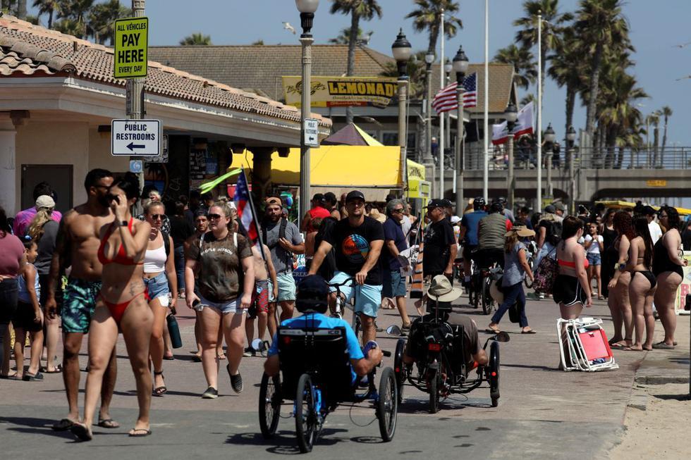 Pocas personas usaban mascarillas el sábado mientras caminaban por un paseo marítimo lleno de gente en Ocean City, en el estado de Maryland. (Reuters/Patrick T. Fallon)