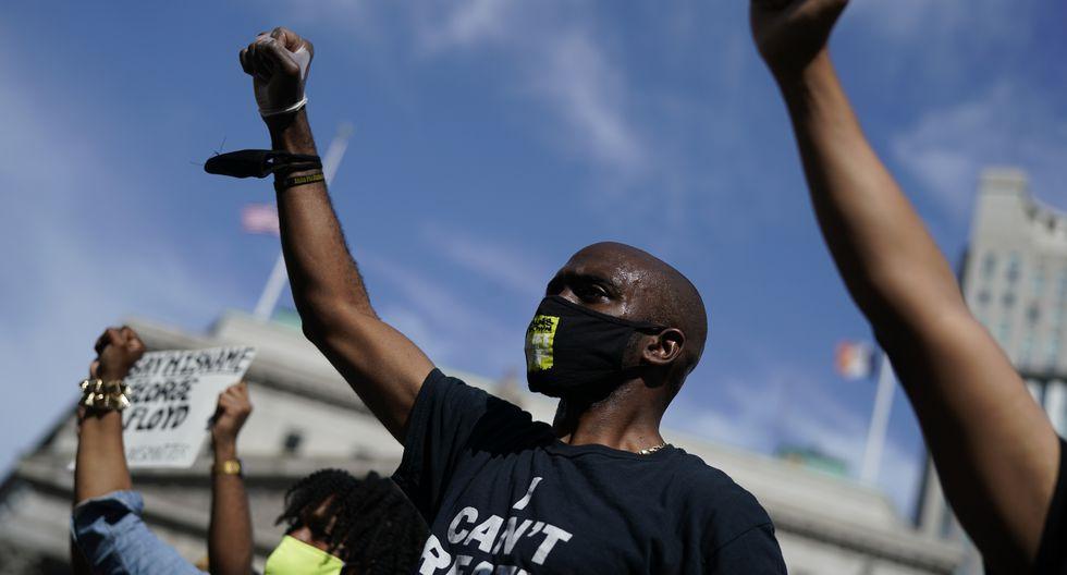 """Manifestantes usan máscaras con el mensaje """"Todavía no puedo respirar"""" durante una vigilia en Foley Square en Nueva York contra la muerte de George Floyd, un hombre afroamericano que murió después de que un policía se arrodilló en su cuello por varios minutos. (Foto: AFP/TIMOTHY A. CLARY)"""