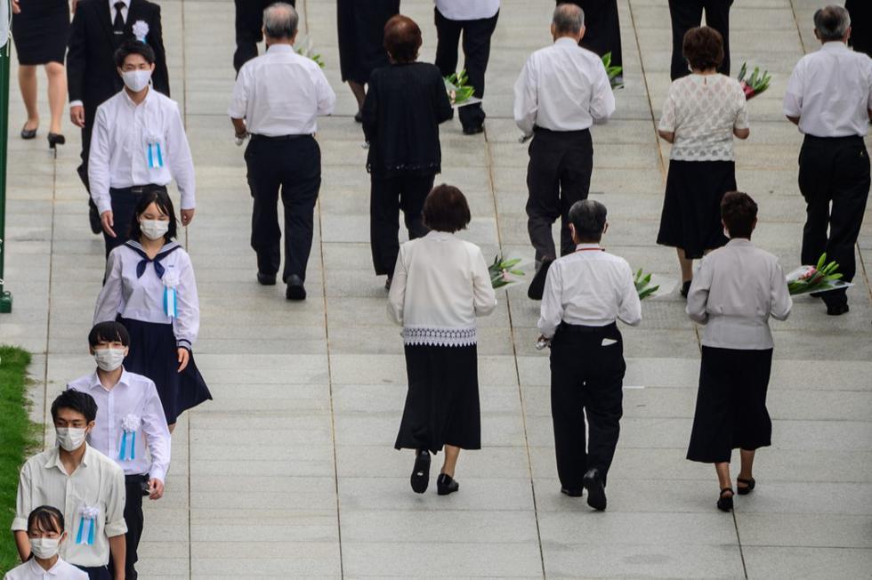 Los participantes del evento llevan flores durante el servicio conmemorativo del 75 aniversario para las víctimas de las bombas atómica, en el Parque Memorial de la Paz, en Hiroshima. (Philip FONG / AFP)