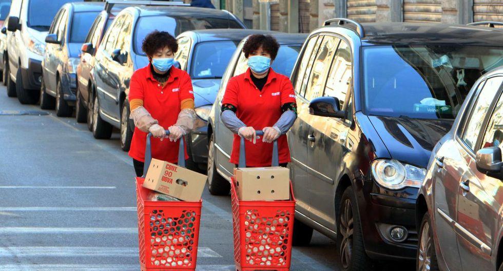 Dos mujeres con mascarillas de protección empujan carritos de compras rojos en la calle Paolo Sarpi, el centro de la comunidad china. (EFE).