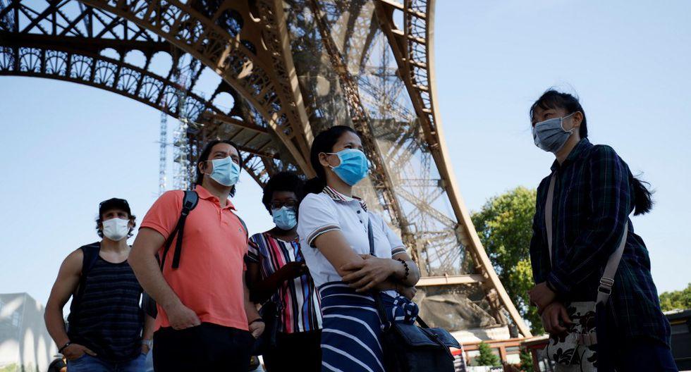 Imagen referencial. Las personas que llevan mascarillas por el coronavirus hacen cola mientras esperan la reapertura parcial de la Torre Eiffel. Archivo del 25 de junio de 2020 en París. (Thomas SAMSON / AFP).